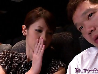 Japanese babe tugging and sucking her mans cock in the public cinema