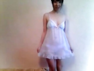 Adorable Asian girlfriend in a silk nightdress gives me and my camera a quick glimpse of her tight pussy in this striptease video we made at home.