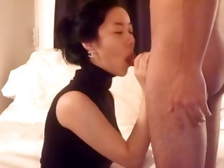 Asian wife in tight sleeveless top kneels before her husband, pulls down his boxer pants and wraps her lips around his cock. Jerking its shaft with he