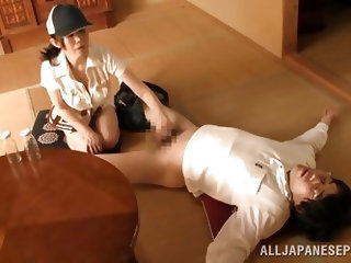 He lays back in the middle of the living room with his pants down and this mature Japanese lady is going to have some fun with him. She jacks him off,