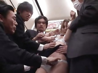 Sexy Asian brunette Rio X is standing in a public train among men. Her short tight dress made those guys real horny and they started groping her altog